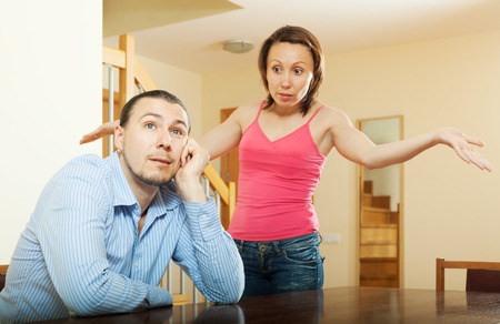 conflict: Family conflict. Tired man listening to his angry woman at home Stock Photo