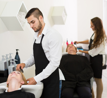 russian hairdresser wash head to the elderly woman in the salon