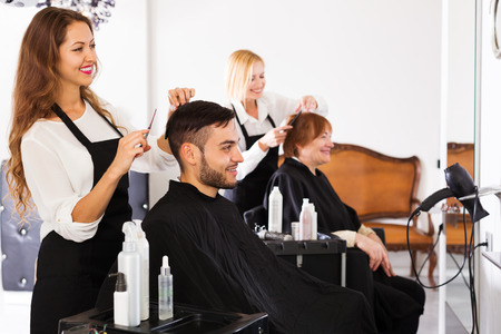 peluquero: El peluquero hace el corte para el hombre joven en la peluquer�a