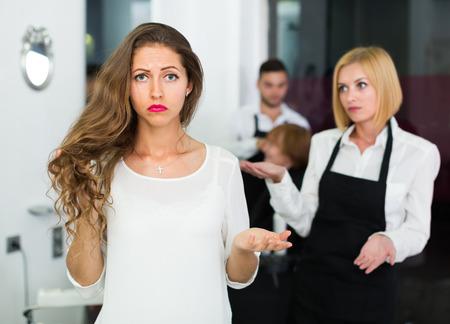 peluqueria: Retrato de infeliz de pelo largo mujer en el salón de peluquería