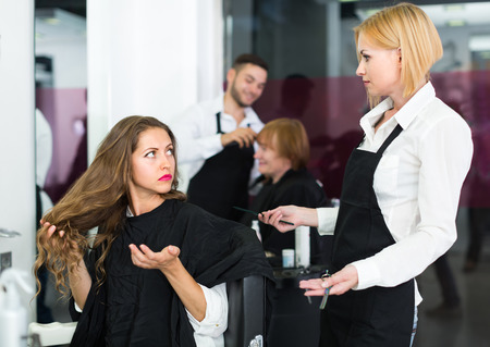 negatively: Angry young longhaired girl negatively talking with the hairdresser