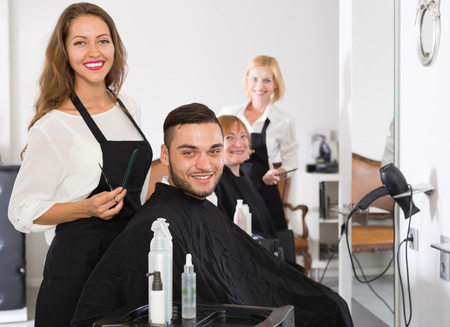 hairtician: Portrait of two hairdressers and two clients in a hair styling salon Stock Photo