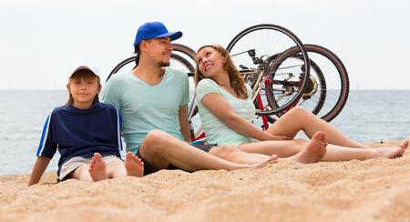 cycles: Familia de tres con los ciclos detr�s en la orilla del mar en d�a de verano
