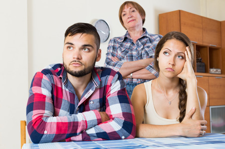 couple talking: Young family quarrels with the husbands mother