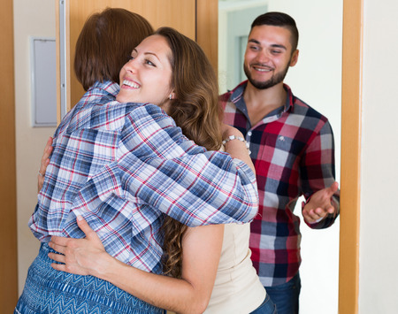 Mature woman meeting  young couple at the door Stock Photo