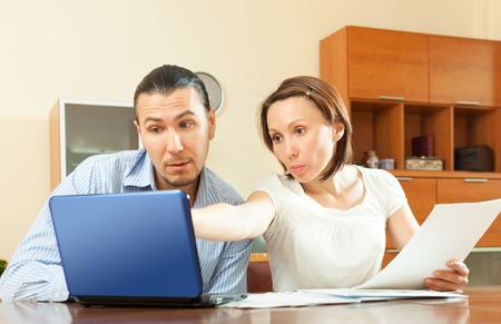 calculated: couple with financial documents and laptop at table in home