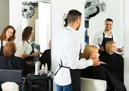barbero: Profesional joven peluquero hace el peinado para los hombres j�venes Foto de archivo