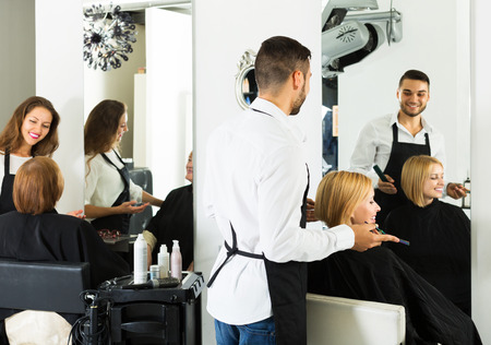 barber shop: Professional young man hairdresser doing hairstyle for young men