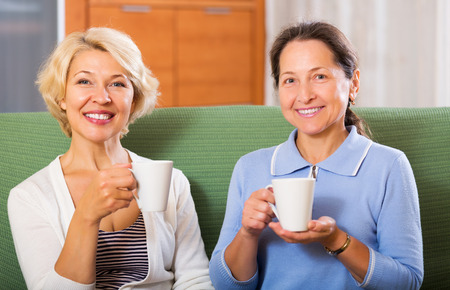 old: Happy elderly female having tea break at office. Focus on blonde woman Stock Photo