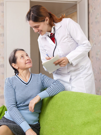 2 50: friendly doctor asks joyful mature patient feels at medical hospital Stock Photo