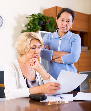 mujer sentada: Sad senior ladies checking invoices at home. Focus on the left woman