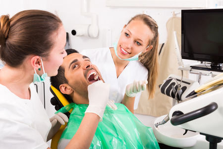 femme bouche ouverte: Dentist with assistant examining the oral cavity of male patient at dental clinic Banque d'images