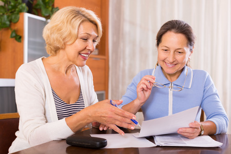 old people reading: Two smiling female pensioners working with documents at the table. Focus on blonde Stock Photo