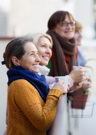 2 50: Group of senior female friends drinking tea at balcony