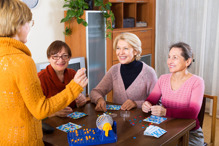 lotto: Positive senior female friends sitting at desk and gaming lotto Stock Photo