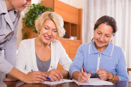 notary: Happy smiling female pensioners signing documents with public notary Stock Photo