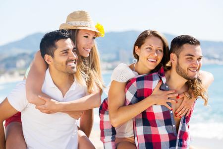 романтика: Улыбающиеся молодые пары обниматься на пляже, наслаждаясь романтикой и солнце