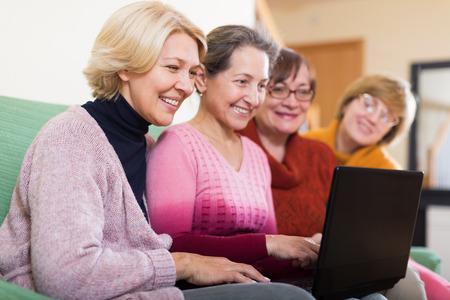 Gelukkig volwassen vrouwelijke browsering internet op de kamer en