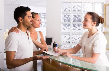 Positive junge Paar mit Sekretärin an der Rezeption in der Klinik im Gespräch