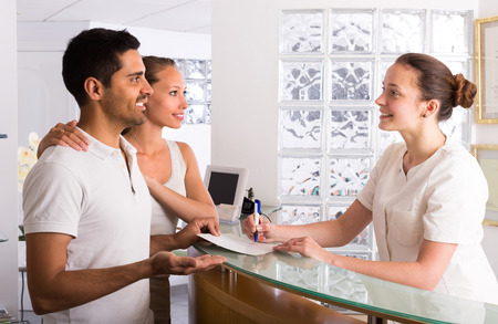 Positive junge Paar mit Sekretärin an der Rezeption in der Klinik im Gespräch Lizenzfreie Bilder