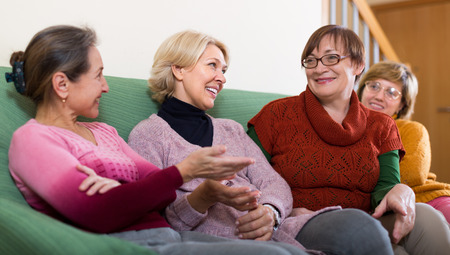 women talking: Smiling female pensioners sitting on sofa and talking. Focus on blonde