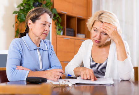 sad old woman: Frustrated senior ladies checking invoices at office.
