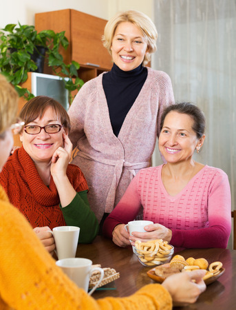 talkative: Elderly women having cup of hot tea indoor and smiling Stock Photo