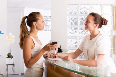 Junge Frau im Gespräch mit dem Sekretär im Büro von Frauen Krankenhaus Lizenzfreie Bilder