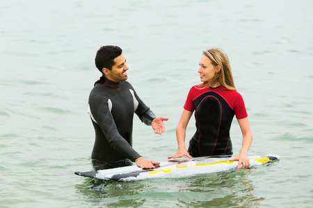 waist deep: Two smiling surfers couple waist deep in sea water
