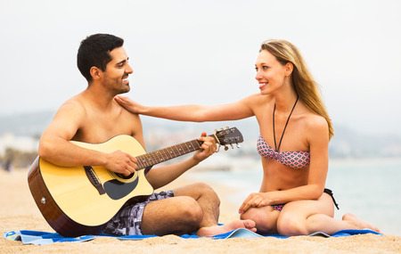 serenading: Young happy couple sitting on the beach with guitar