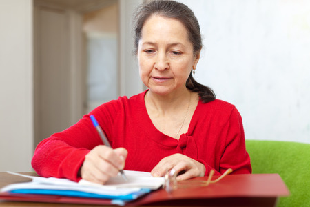 calculated: mature woman fills in the questionnaire at  home
