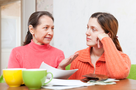 mother helps adult daughter  to fills in  utility payments bills. Focus on mature