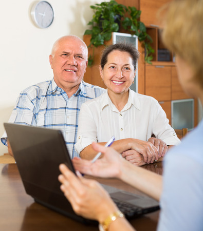 census: Aged smiling couple talking with employee with laptop at home. Focus on woman