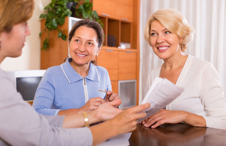 consulting room: Positive senior ladies signing documents at bank with agent. Focus on brunette Stock Photo