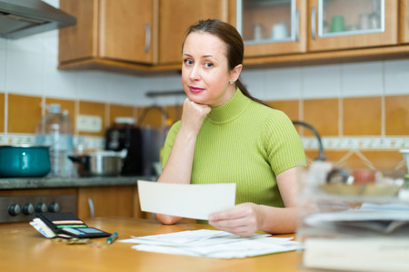 ordinary woman: Ordinary woman sitting with financial documents at the table in kitchen