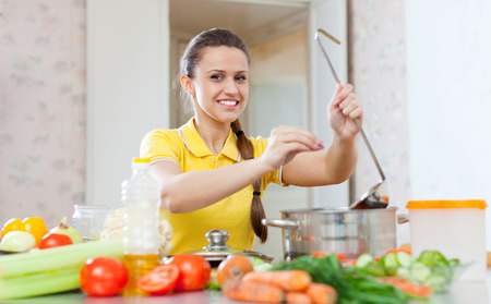 adds: woman adds spice or salt in saucepan at kitchen