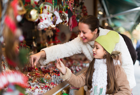 Smiling mother with positive girl in Christmas market. Focus on girl Archivio Fotografico