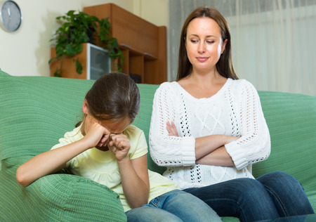 discipline: Woman berating frustration daughter in home interior Stock Photo