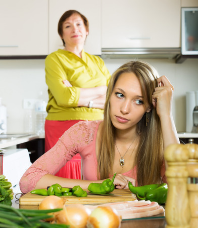 admonition: Mature mother and sad adult daughter having quarrel   in kitchen