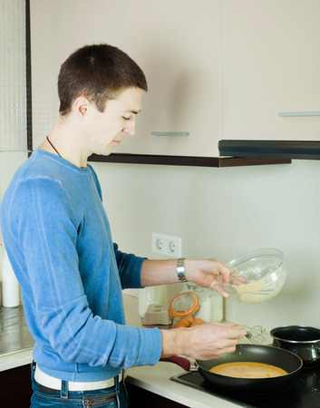 fryingpan: Guy making scrambled eggs in frying pan at home kitchen Stock Photo