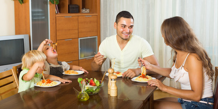 gladful: Smiling young family of four eating with spaghetti at table. Focus on man