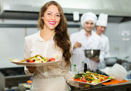 commercial kitchen: Team of chefs and young beautiful waiter at restaurant kitchen Stock Photo