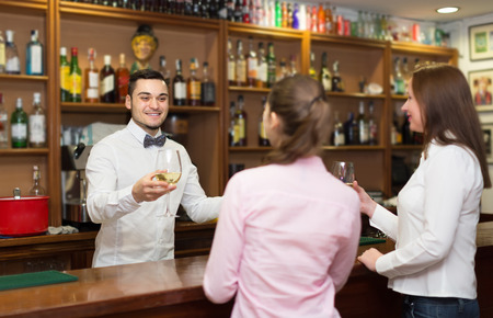 barmen: Two girls flirting with happy smiling handsome barman at bar