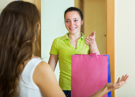 cognate: Positive girl visiting her girlfriend with gift