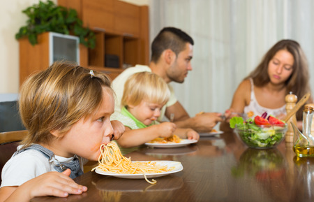 gladful: Young family with playful little daughters eating with spaghetti at table. Focus on girl