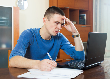 parsimony: Sad frustrated guy looking at financial documents in laptop in home interioк sitting by table
