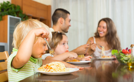 having lunch: Happy young parents with children having lunch with spaghetti at home together. Focus on girl
