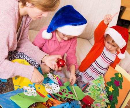 4s: nanny helping little daughters  to make decoration for Xmas Stock Photo