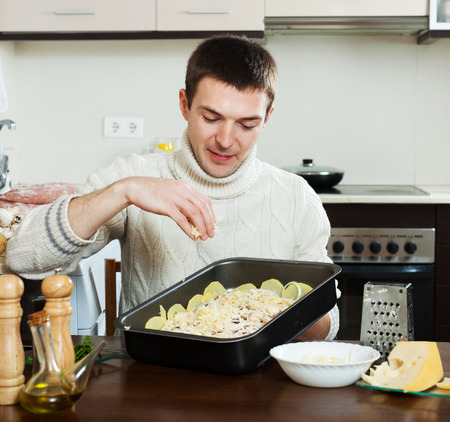 roasting pan: Smiling guy cooking french-style meat. Adding grating cheese in roasting pan