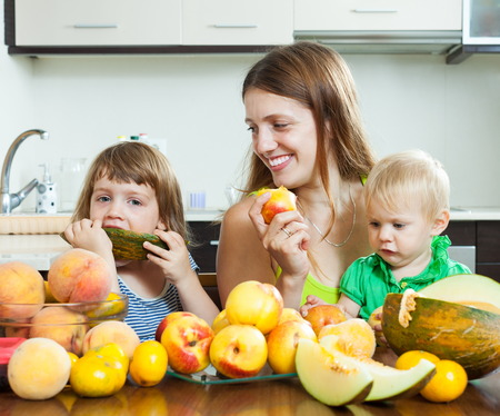 over eating: Happy woman with children eating melon and other fruits over  table at home interior Stock Photo